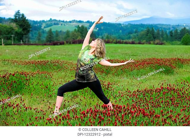 A woman does yoga in a field of wildflowers with mountains in the background; Oregon, United States of America
