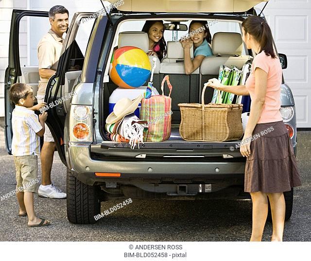 Hispanic family loading car for trip