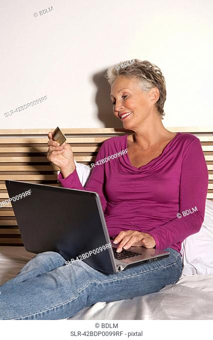 Older woman shopping online on bed