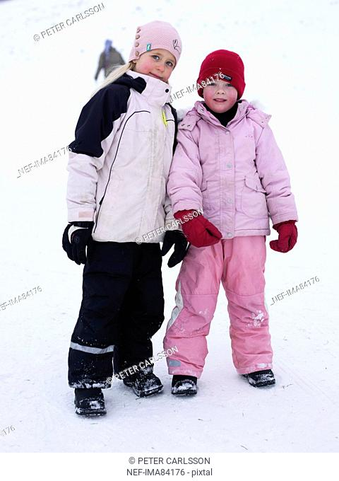 Two children standing together in snow