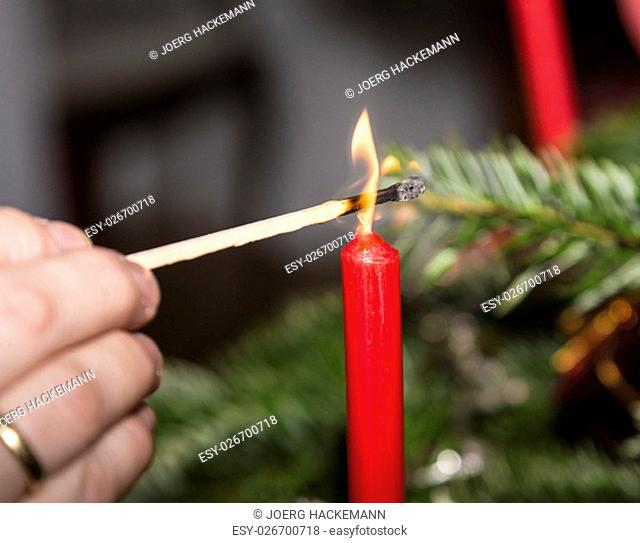 Lightning the candles at the christmas tree with matches