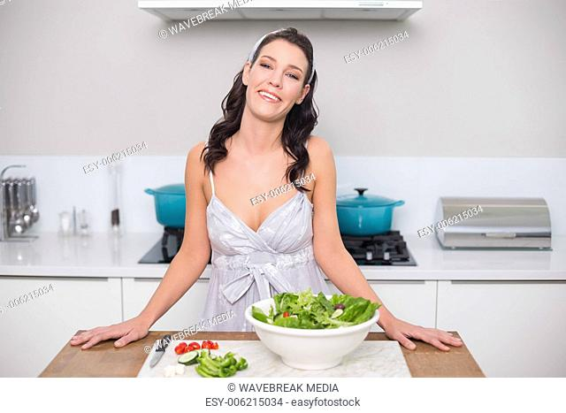 Cheerful pretty brunette making salad
