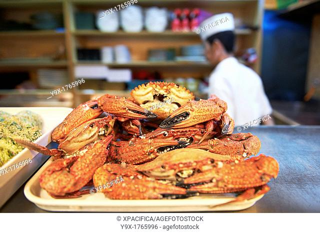 Fresh crab on display on a counter while a chef works in a kitchen behind