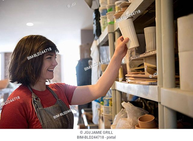 Smiling Caucasian woman placing cup on shelf in workshop