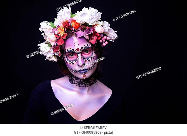 Fashion portrait of a beautiful Halloween model with creative make up, rhinesto