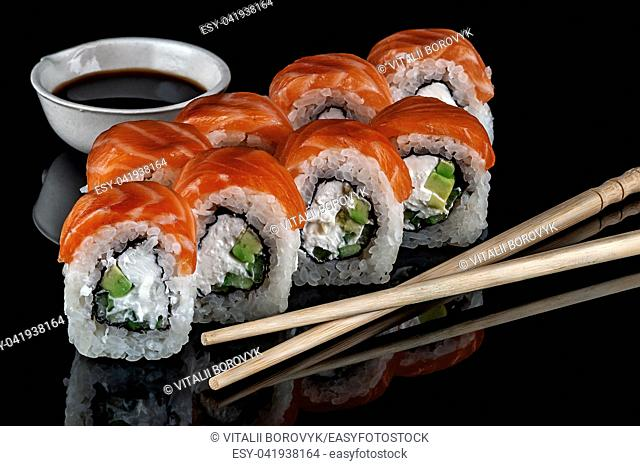 Philadelphia sushi rolls with chopsticks and soy sauce. Black background. Reflection