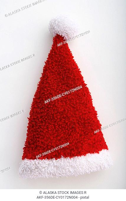 Closeup of small Santa Claus hat with tassel outstretched on white background studio portrait