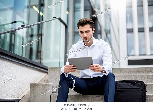 Businessman sitting on stairs with earbuds and tablet