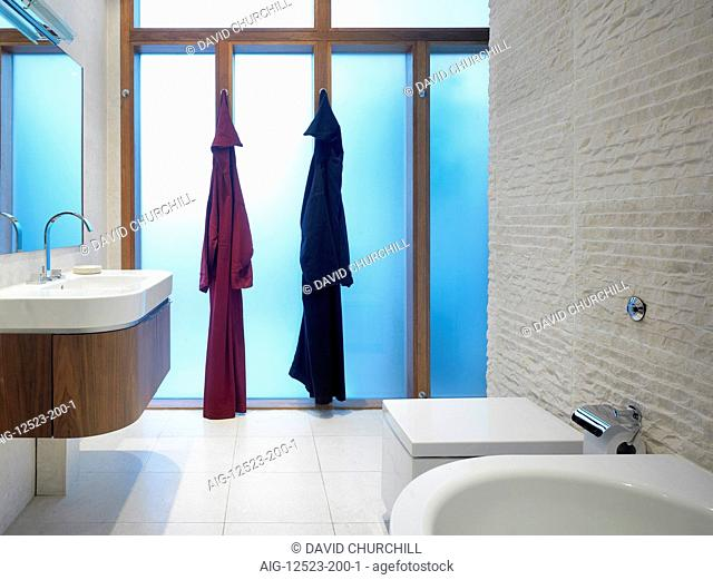 Two bath robes hanging in a modern bathroom
