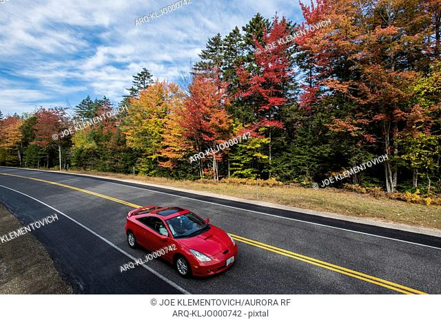 A red car driving through New Hampshire's bright and colorful fall foliage