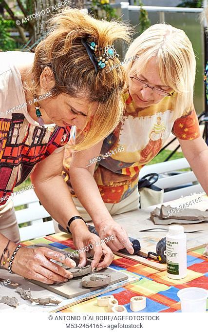 Amateur artists while modeling clay to obtain raku ceramics