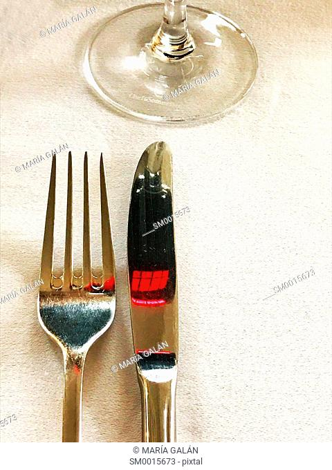 Fork, knife and glass of red wine reflected on the knife