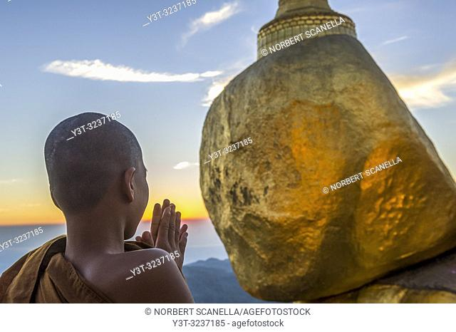 Myanmar (formerly Burma). Kyaiktiyo. State Mon. Sacred site of the golden rock. Young novice praying