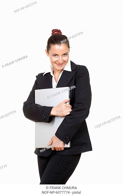 Smiling businesswoman holding a laptop