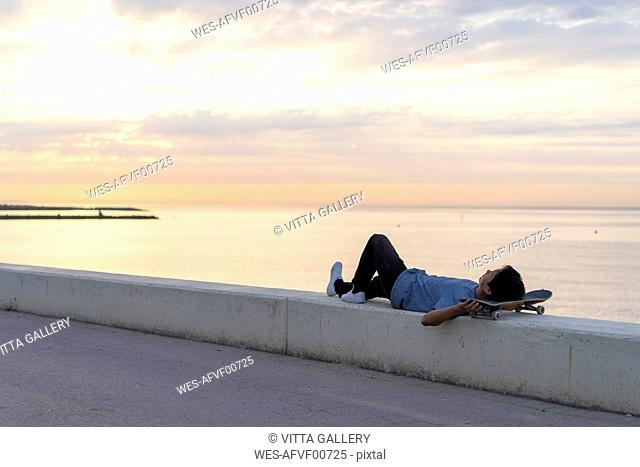 Young Chinese man with skateboard lying on wall at the beach