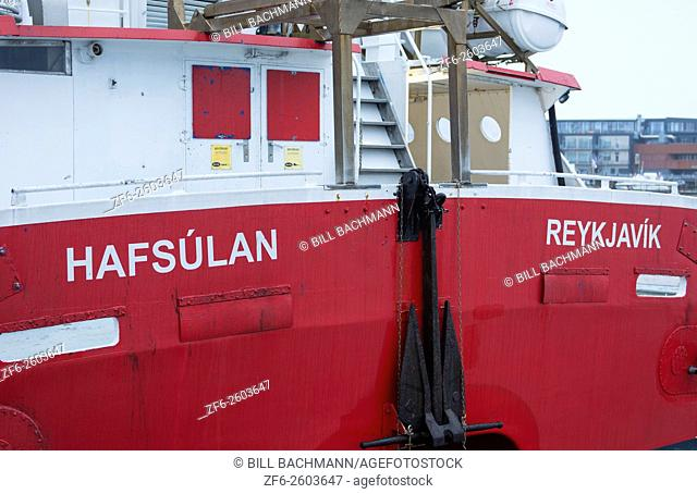 Reykjavik Iceland red fishing boat in harbor of marina closeup abstracts of ship for lobsters and fishing