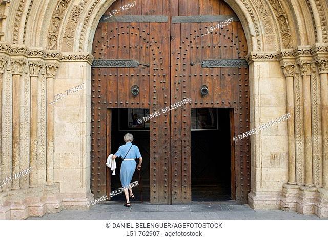 Old woman walking into the most famous church in Valencia, la Catedral de Valencia, Valencia, Comunidad Valenciana, Spain