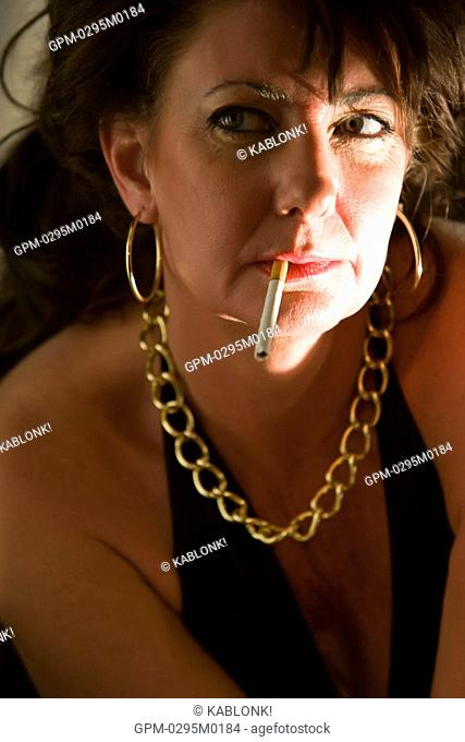 Portrait of woman in gold jewelry with cigarette in mouth