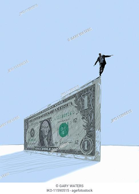 Businessman balancing at the edge of large dollar banknote
