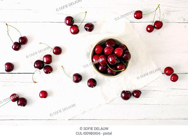 Overhead view of black cherries in bowl and scattered on surface