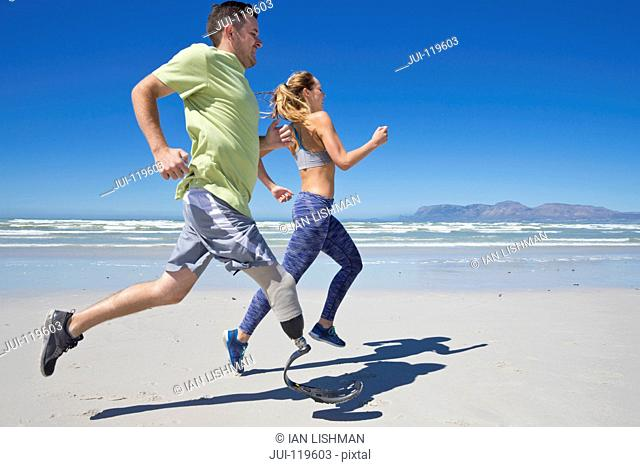 Side View Of Man Wearing Prosthetic Blade Running Along Shoreline Of Beach With Female Partner