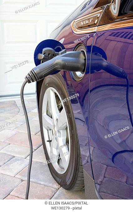 Plug-in electric car with connector plugged in charging, at home in a driveway at home in a driveway