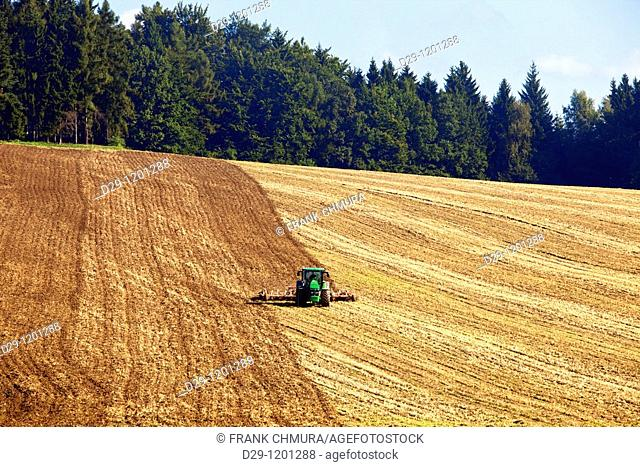 czech republic, bohemia - tractor plowing field