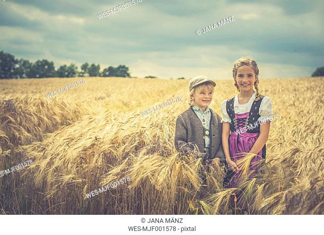 Germany, Saxony, two children standing in a grain field