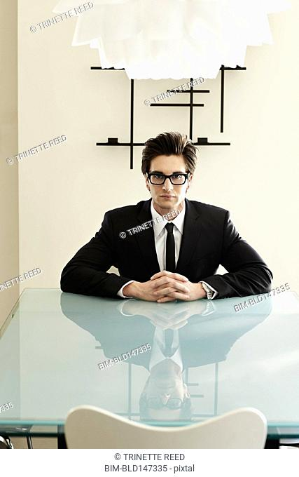 Trendy Caucasian businessman sitting at conference table