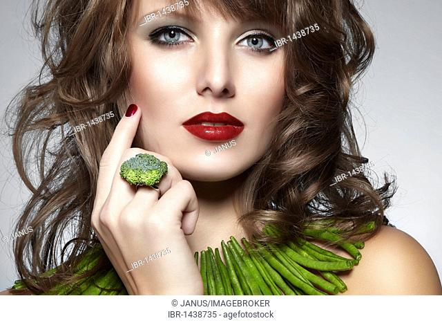 Portrait of a young woman with green beans as a necklace and a ring of broccoli, jewelry