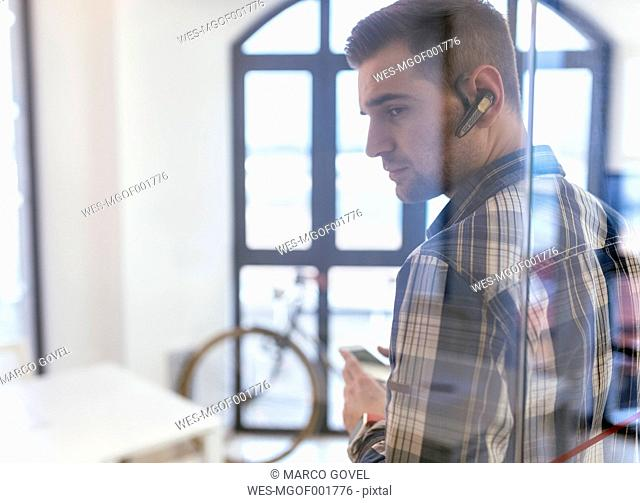 Young man wearing bluetooth headset in office