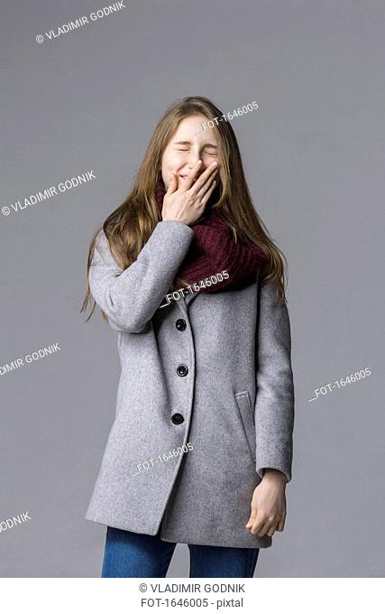 Smiling teenage girl covering mouth standing against gray background