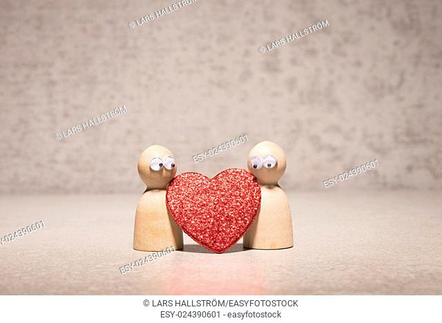Couple holding red heart. Wooden figures with cute and funny symbol of love. Concept of romantic feelings, dating insecurity and valentine celebration