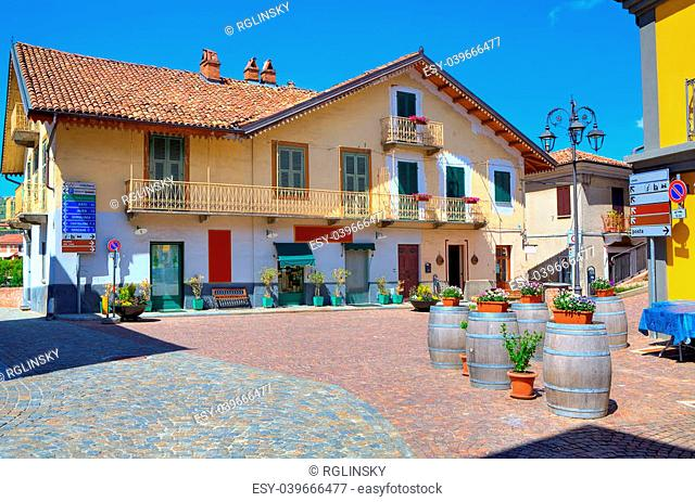 View of small cobblestone plaza at the center of typical italian town among colorful houses in Barolo, Italy