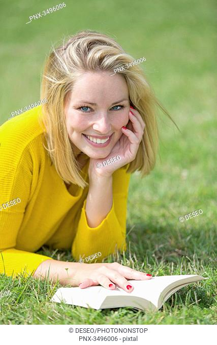 Blonde pretty woman reading a book in park smiling at camera