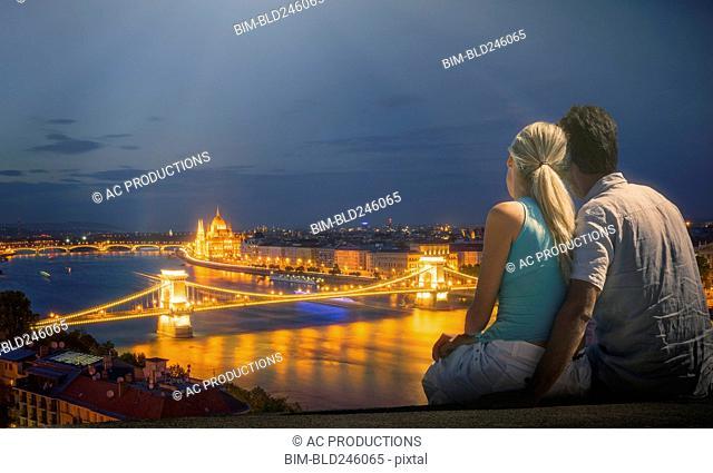 Caucasian couple admiring scenic view of bridge at night