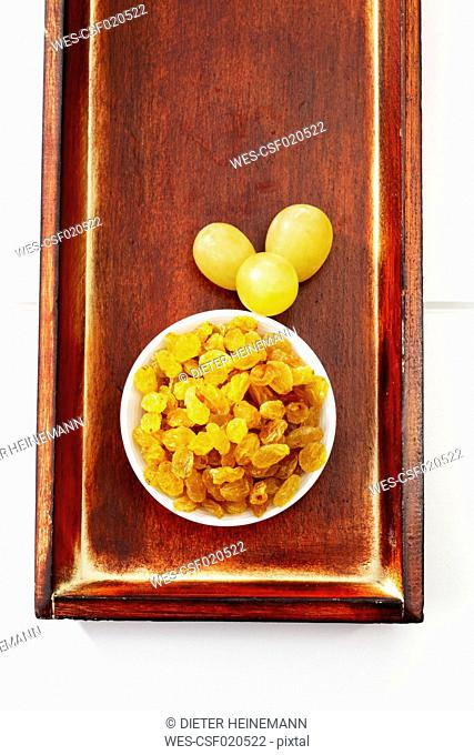 Bowl with sultanas and three green grapes on wooden tray
