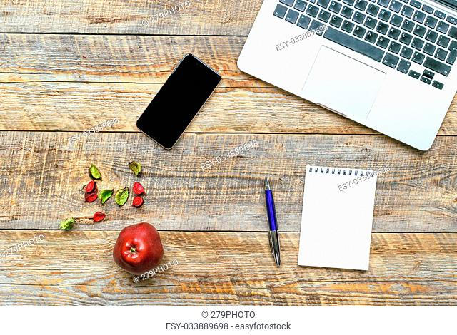 Comfortable working place, wooden table with laptop, phone and red fruit