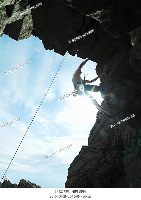 Rock climber scaling steep rock face