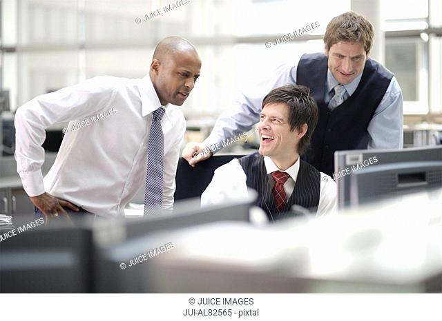 Three businessmen talking at desk