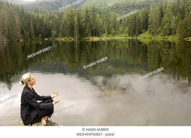 Businesswoman meditating at lake, side view
