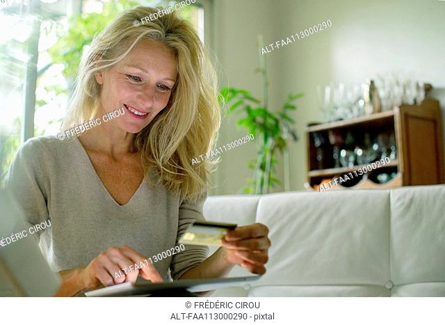 Mature woman using digital table to shop online