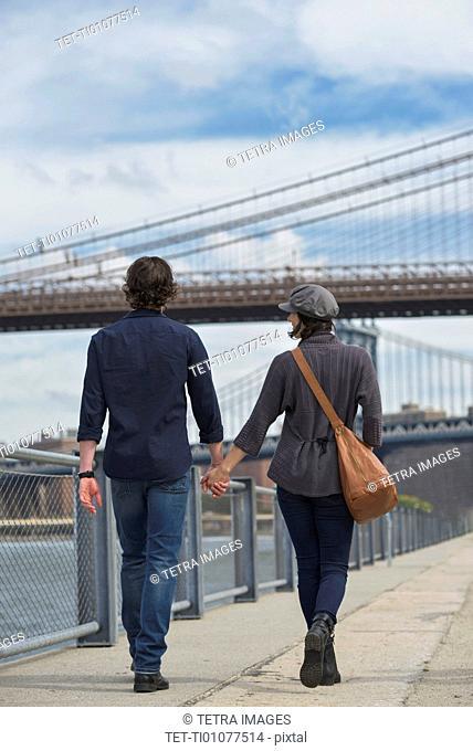Rear view of couple walking on promenade, Brooklyn Bridge in background