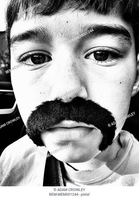 Close up portrait of Caucasian boy wearing fake mustache