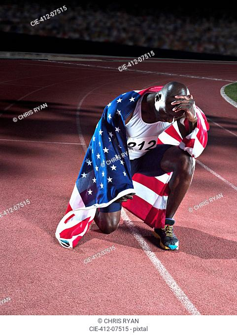 Track and field athlete wrapped in American flag on track