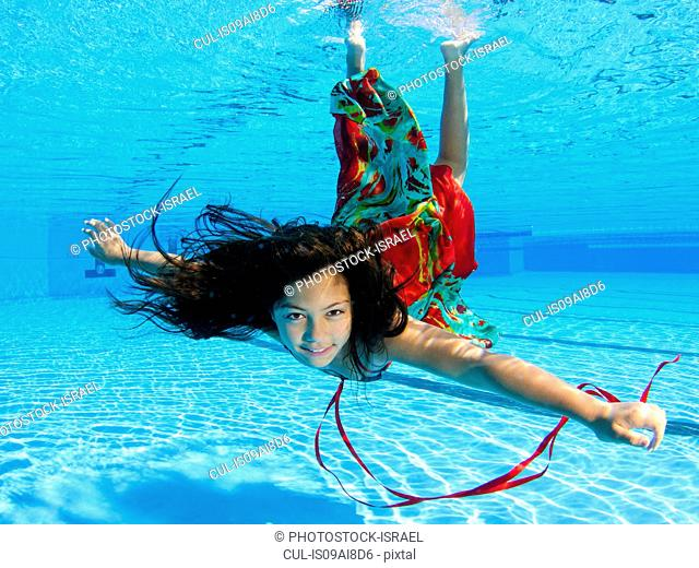 Girl free diving under water in swimming pool