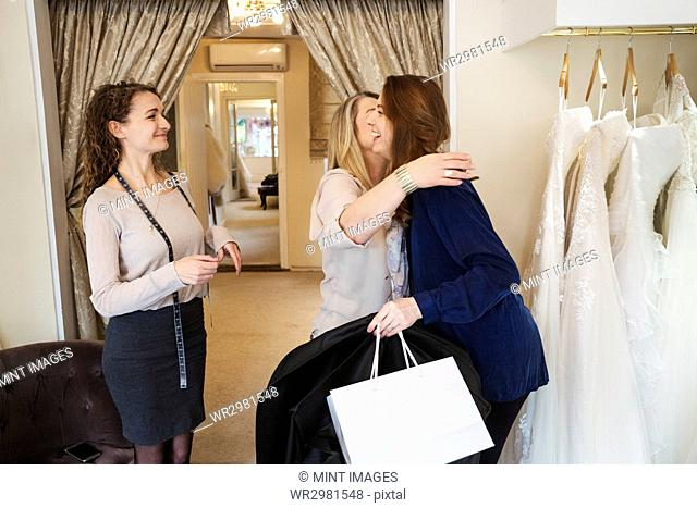 Three women in a wedding dress shop, one hugging and greeting a customer. A bridal boutique
