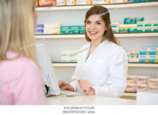 Portrait of smiling female pharmacist advising female customer
