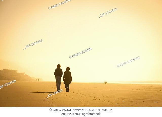 Two women walking on the beach on a foggy winter day; Yachats, central Oregon coast