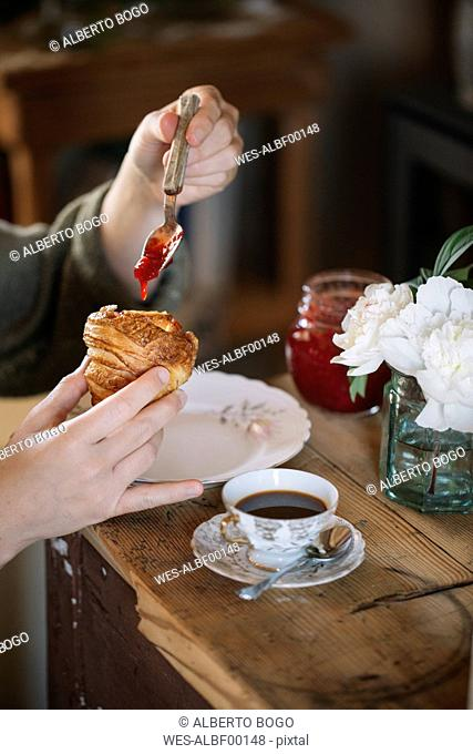 Close-up of woman tasting homemade croissants with jam